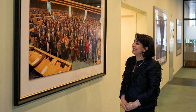 President Arib standing next to a group photo of the House prior to the 2017 Elections.