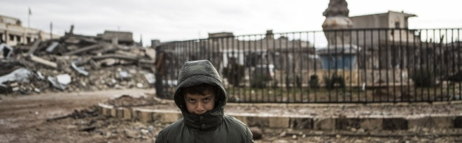 Child with a heavily bombed cityscape of Kobane, in northern Syria.