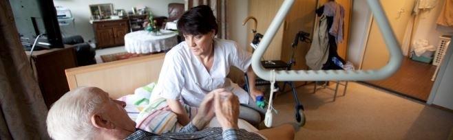 Community nurse assists an elderly man at home